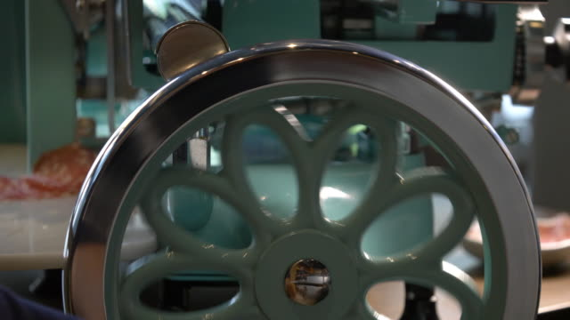 vidéos et rushes de charcuterie meat being sliced in a delicatessen on a hand operated italian enamel fly wheel slicer - anorexie nerveuse