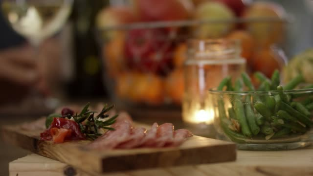 charcuterie on a wood cutting board with peppers, green beans, fruit basket and a lit candle - cutting board stock videos and b-roll footage