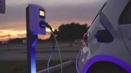 SLO MO Charging a car at charging station at dusk