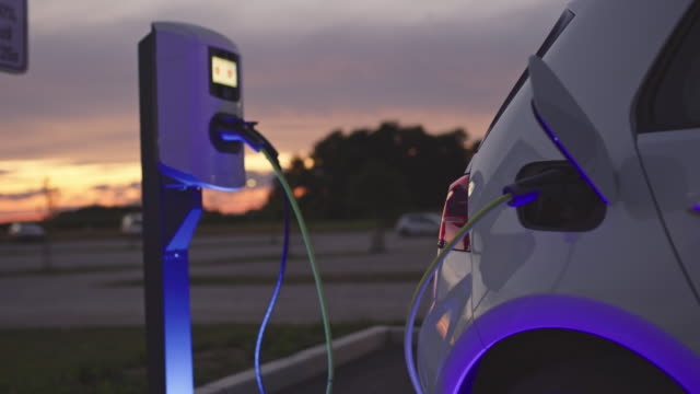 vídeos de stock e filmes b-roll de slo mo charging a car at charging station at dusk - transportation