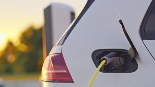 vidéos et rushes de slo mo charge d'une voiture à la station de recharge au coucher du soleil - ligne à haute tension