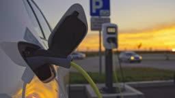 SLO MO Charging a car at charging station on a parking lot at dusk