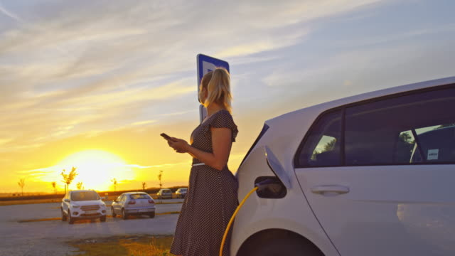 vídeos y material grabado en eventos de stock de slo mo cargando un coche en la estación de carga al atardecer - coche híbrido