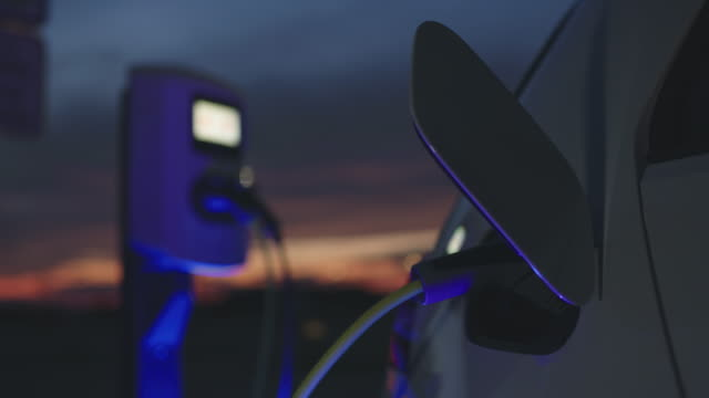 slo mo charging a car with blue energy at dusk - energy efficient stock videos & royalty-free footage