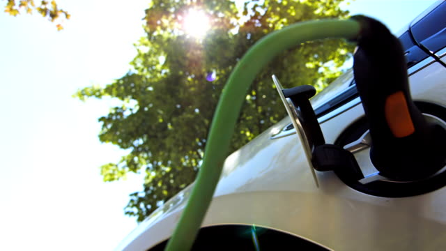 hd: charging an electric car under green trees - electric vehicle stock videos & royalty-free footage