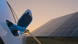 SLO MO Charging an electric car with blue energy coming from solar panels