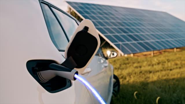 vidéos et rushes de slo mo charge d'une voiture électrique avec de l'énergie bleue à partir de panneaux solaires - ligne à haute tension