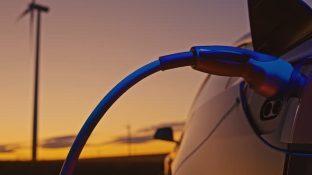 vidéos et rushes de slo mo charge d'une voiture électrique avec de l'énergie bleue des éoliennes - ligne à haute tension