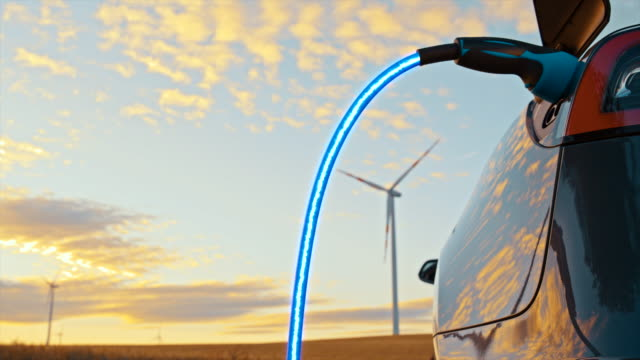 slo mo laddar en elbil med blå energi från vindkraftverk - hållbar energi bildbanksvideor och videomaterial från bakom kulisserna