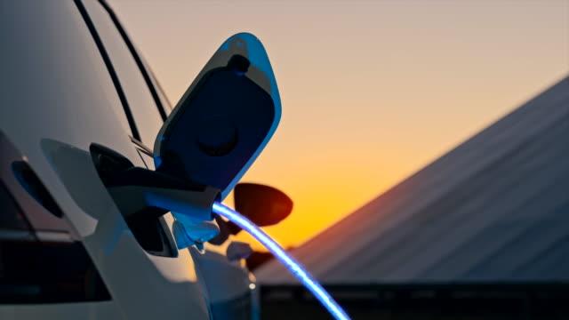 vidéos et rushes de slo mo charge d'une voiture électrique avec de l'énergie bleue en passant par le câble ev - charger activité