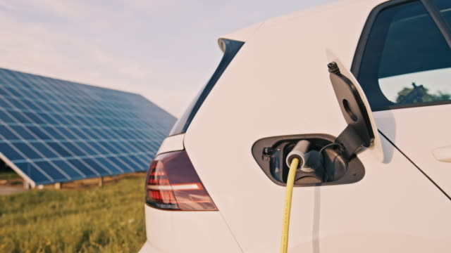 slo mo charging an electric car with green energy from solar panels - wired stock videos & royalty-free footage