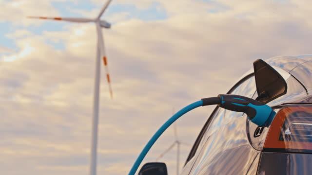 slo mo aufladen eines elektroautos mit grüner energie aus windkraftanlagen - windenergie stock-videos und b-roll-filmmaterial