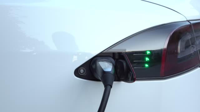 CLOSE UP: Charging cable plugged into luxury electric car, filling battery at home