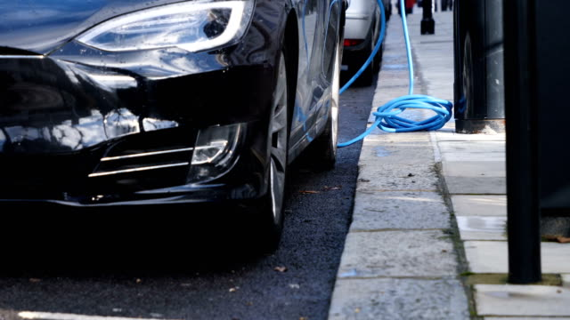 charging electric car on the street. - electric car stock videos & royalty-free footage