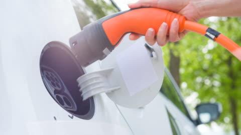 vídeos y material grabado en eventos de stock de carga de vehículo eléctrico híbrido bajo los árboles verdes - vehículo eléctrico