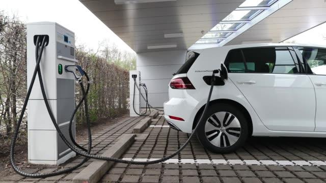 vídeos de stock, filmes e b-roll de charging plugs sit connected to an electric charging station outside the volkswagen ag factory in dresden germany on monday april 3 2017 - posto de carregamento de veículos elétricos