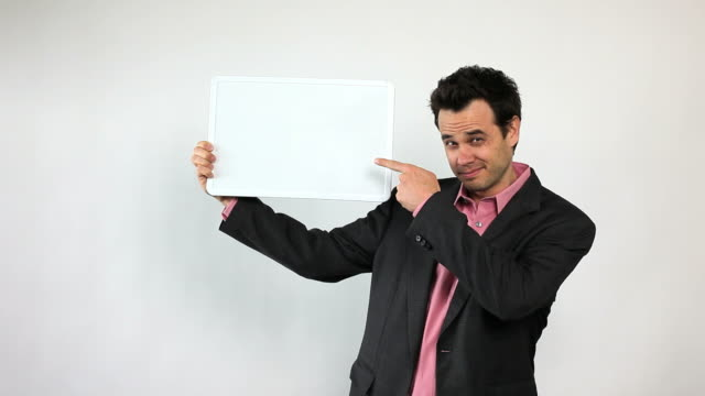 charismatic sales guy holding white board, pointing and smiling. - banner sign stock videos & royalty-free footage
