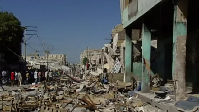 charities receive funding warning after oxfam abuse allegations t14011026 / 1412010 portauprince ext people around ruins of building destroyed in... - haiti stock videos & royalty-free footage