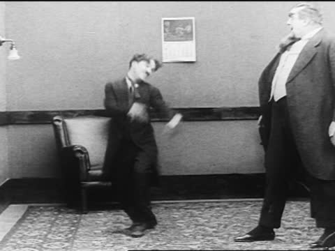 charle chaplin dancing to avoiding fighting with large man / man punches him - 1916 stock videos & royalty-free footage