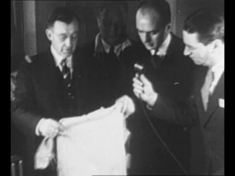 Charles A Lindbergh walks with others inside courtroom / montage men with baby's sleeping garment tagged as evidence in kidnapping of Lindbergh's son...