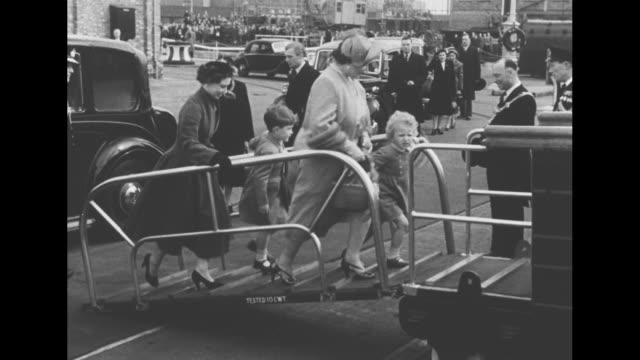 Charles and Anne with grandmother Queen Mother Elizabeth and aunt Princess Margaret behind them walk along platform at Portsmouth train station the...