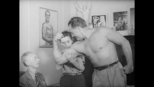 charles atlas demonstrates strenth to older man and boy / a shirtless atlas holds biceps up to show muscles and rips a phonebook in half - body building stock videos & royalty-free footage