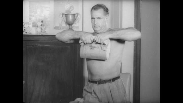 charles atlas talking to older man and 2 young men / atlas takes his shirt off and holds biceps up to show muscles and tries to rip phonebook in half... - body building stock-videos und b-roll-filmmaterial