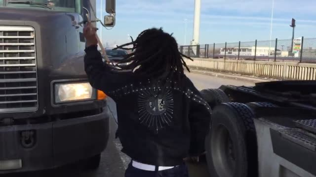 Charles Chaplin a Chicago southside teen uses a paint bucket as a drum and plays as he walks between vehicles exiting the I90 EastBound onto Garfield...