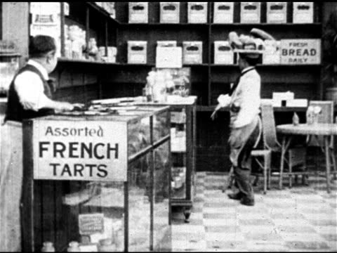 charles chaplin 'dough and dynamite' film can onto shelf: clip: comedic actor charlie chaplin in bakery balancing bread tray on head, dropping... - 1914 stock videos & royalty-free footage