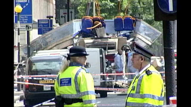 charles clarke criticises 42day detention bill tx ambulance along and police officers police officers standing near wreckage of bombed no 30... - gefangen stock-videos und b-roll-filmmaterial