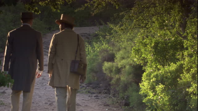 charles darwin and nicholas lawson walk side by side on a sandy path through the trees. available in hd. - チャールズ・ダーウィン点の映像素材/bロール