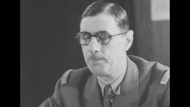 vidéos et rushes de charles de gaulle, president of free french committee, sitting at desk in front of microphone holding speech in hand; he is not wearing his usual... - londres