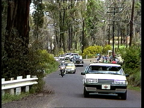 charles & diana in australia: day 5; australia: victoria: macedon royal motorcade along road towards, forest of trees in background - day 5 stock videos & royalty-free footage