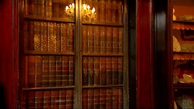 vídeos de stock e filmes b-roll de dickens world / gad's hill place close shots of leatherbound books on shelf / books in glassfronted bookcase / people going through bookcase / door... - charles dickens