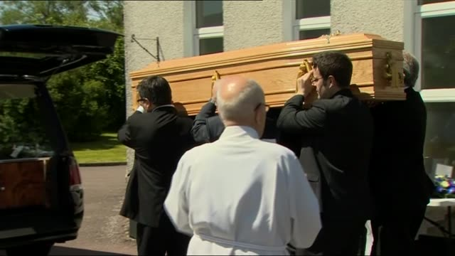 arrivals / coffin carried out of church bagpiper playing sot / coffin of charles kennedy being carried out of church and along to hearse / mourners... - charles kennedy stock videos & royalty-free footage