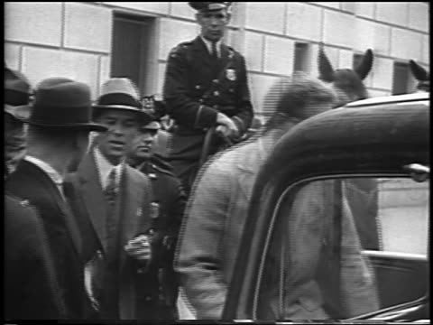 vidéos et rushes de charles lindbergh entering car as police look on at kidnapping trial / newsreel - 1935