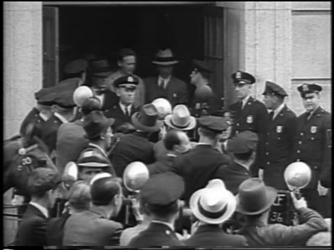 vidéos et rushes de charles lindbergh exiting courthouse past crowd of reporters at kidnapping trial / newsreel - 1935