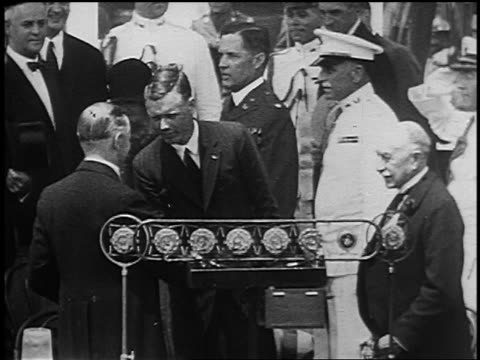 Charles Lindbergh shaking hands with Calvin Coolidge by microphones after historic flight