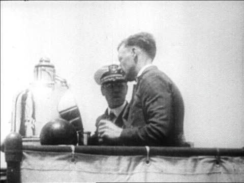Charles Lindbergh talking to naval officer on board ship to US / newsreel