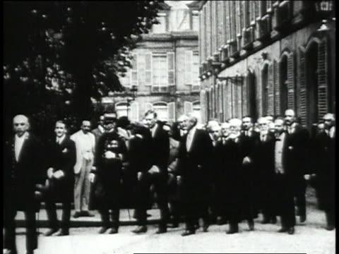 Charles Lindbergh walking down street with several men / Paris France