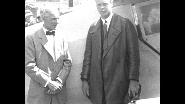 charles lindbergh's plane lands in grassy field / he climbs down from cockpit, wearing flight helmet and goggles / lindbergh greets henry ford; the... - ヘンリー・フォード点の映像素材/bロール