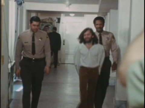 of charles manson wearing plain clothes and walking down a hallway with hands cuffed behind his back. he is being followed by two police officers in... - hinrichtung stock-videos und b-roll-filmmaterial
