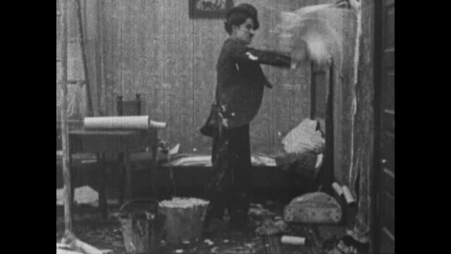 vídeos de stock, filmes e b-roll de 1915 charlie chaplin angrily flings wallpaper paste at wall while his boss cleans himself off and lectures - charlie chaplin