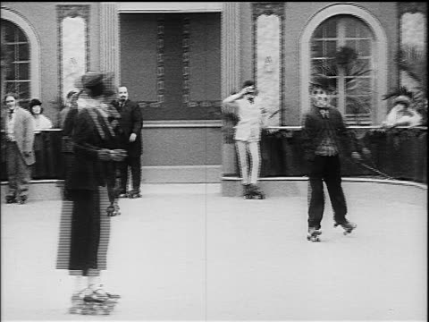 charlie chaplin as little tramp roller skating colliding with other man - 1916 stock videos & royalty-free footage