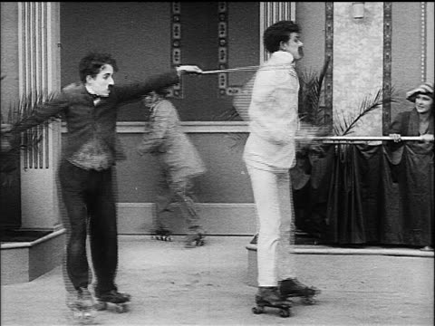 charlie chaplin as little tramp roller skating knocking over other men - 1916 stock videos & royalty-free footage