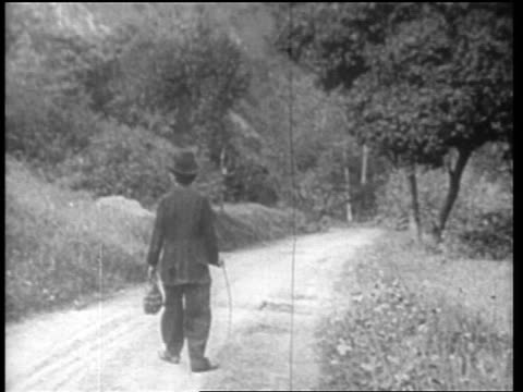 vídeos de stock, filmes e b-roll de charlie chaplin as little tramp walking down country road - cena não urbana