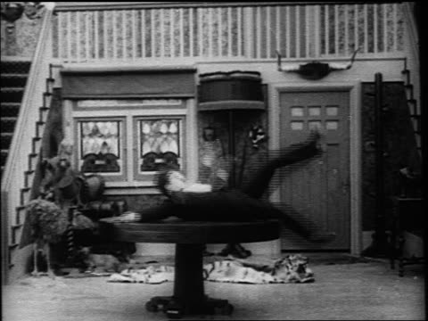 charlie chaplin balancing on spinning table then losing balance falling to floor - 1916 stock videos & royalty-free footage