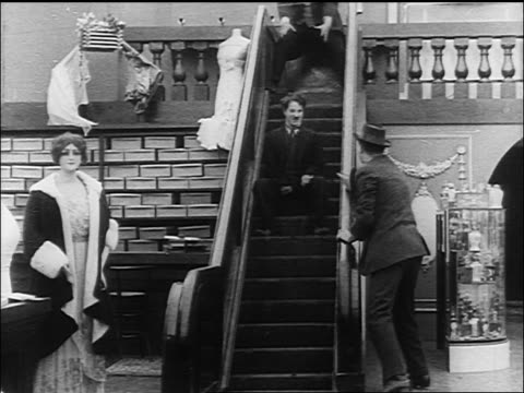 charlie chaplin being chased down the up escalator by large man - 1916 stock videos & royalty-free footage