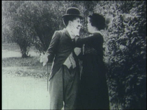 Charlie Chaplin has arm around woman she slaps him in face