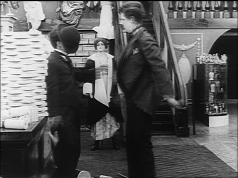 charlie chaplin man pushing each other in department store / man falls - 1916 stock videos & royalty-free footage